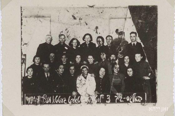 Kuchnia ludowa, marzec 1941 r. Zdjęcie grupowe pracowników. W pierwszym rzędzie od dołu druga kobieta od prawej - Regina Rumkowska, żona Chaima Rumkowskiego. Zbiory ŻIH